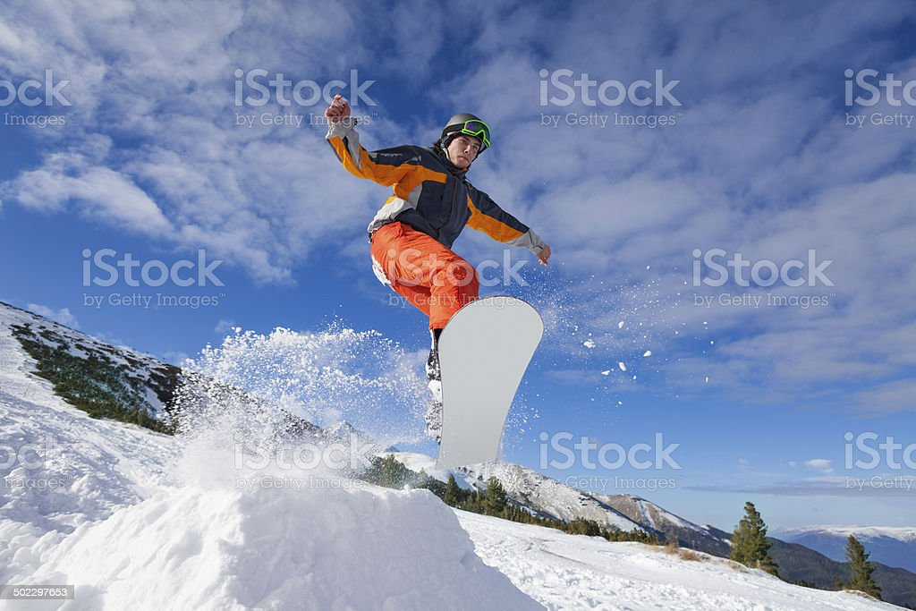 Man jumping with snowboard from mountain hill stock photo