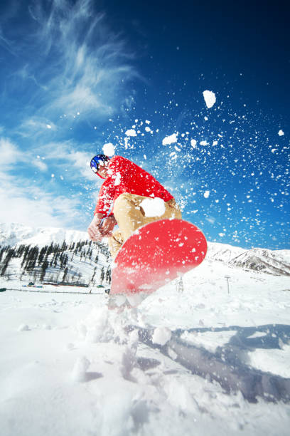 Man jumping with snowboard stock photo