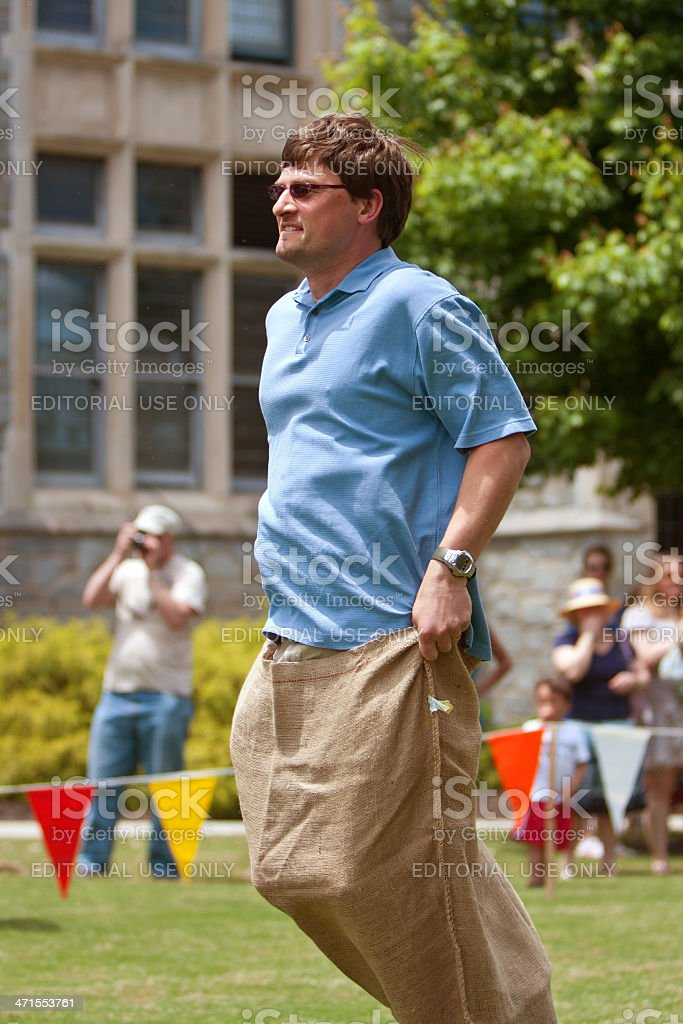 Man Jumps Along In Sack Race At Spring Festival stock photo