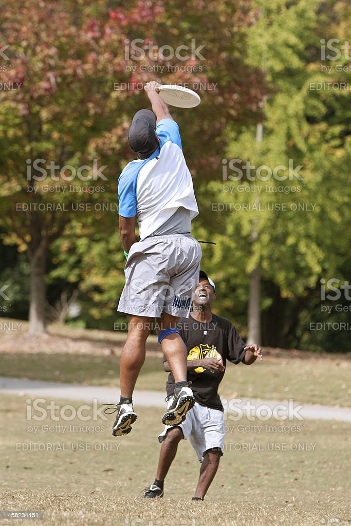 Man Jumps High To Catch Disc In Ultimate Frisbee Game stock photo