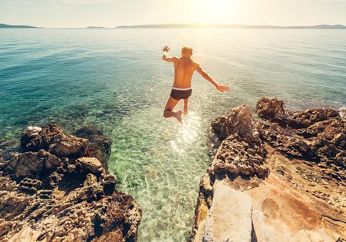 istock Man jumps in blue sea lagune water 641064846