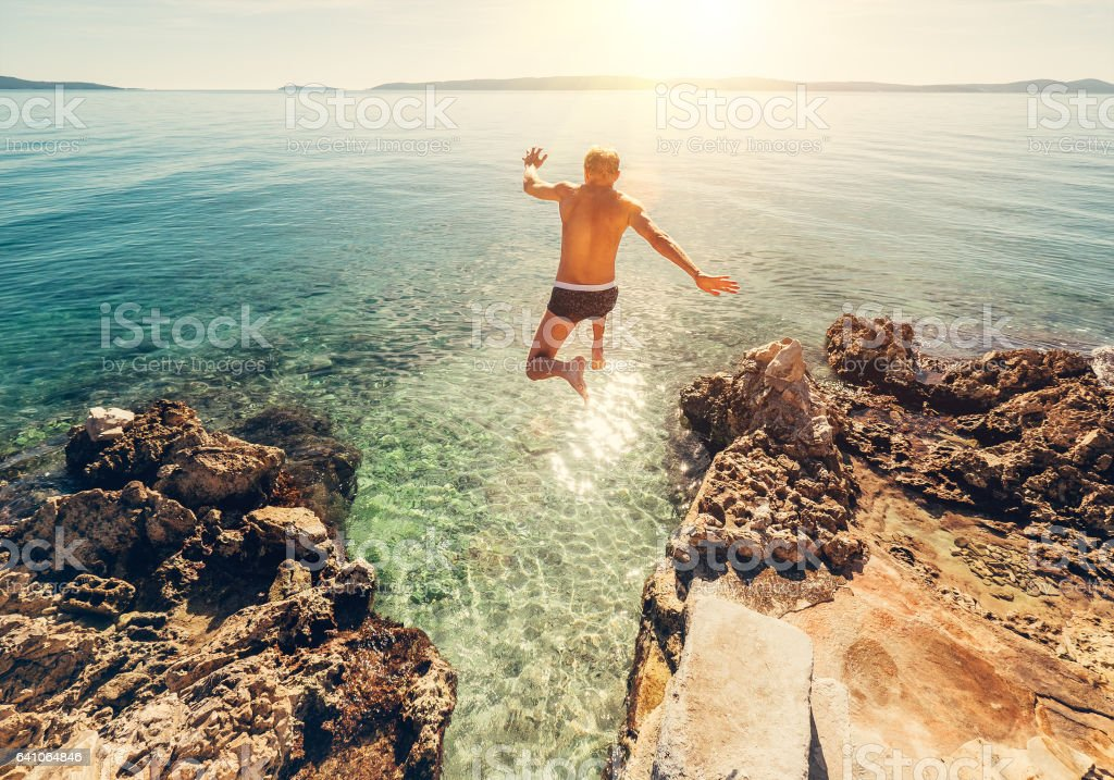 Man jumps in blue sea lagune water stock photo