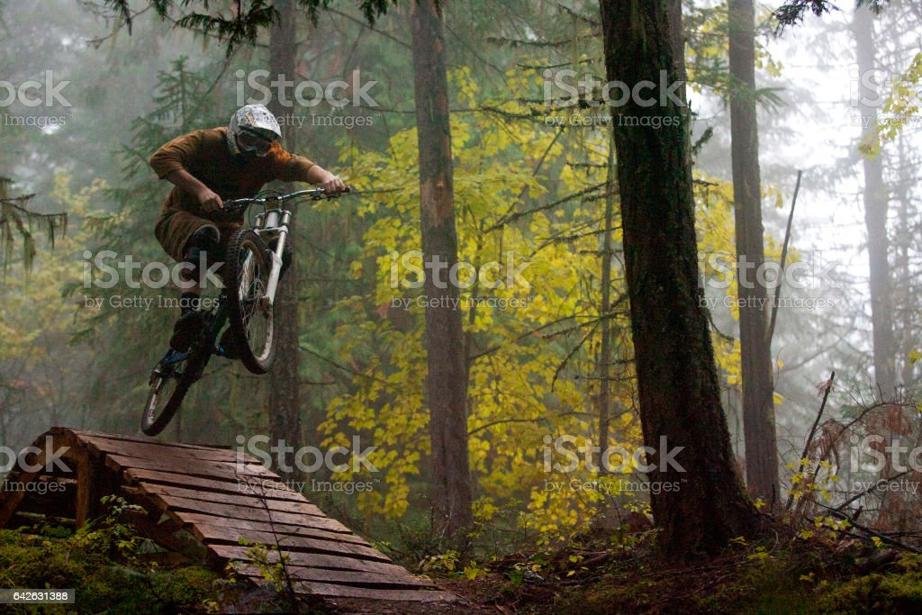 A man jumps off a wooden bridge on his downhill mountain bike on a foggy day in British Columbia, Canada.