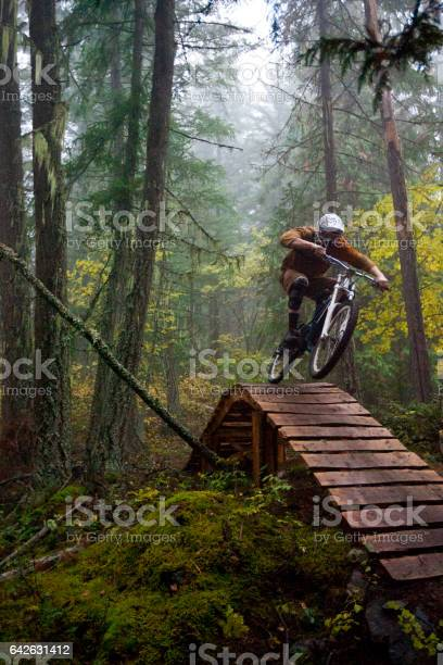 Photo of A man jumps off a wooden bridge on his downhill mountain bike on a foggy day in British Columbia, Canada.