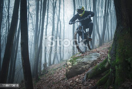 A teenager rides a mountain bike in the foggy forest, he jumps off from the big stone.
