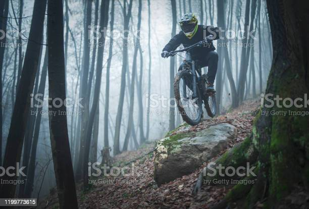 Photo of A man jumps off on the his Enduro mountain bike in a foggy day in the forest.