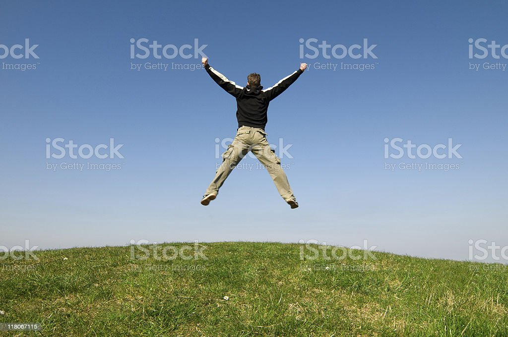 Man jumps with joy on top of a green hill stock photo