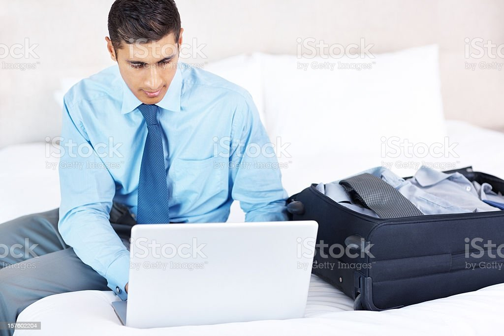 Man just arrived to hotel room and working on laptop royalty-free stock photo