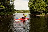 50 + man kayaking on a lake. He is wearing hat and  black t-shirt over swimwear, and is enjoying his vacations. Horizontal full length outdoors shot with copy space.