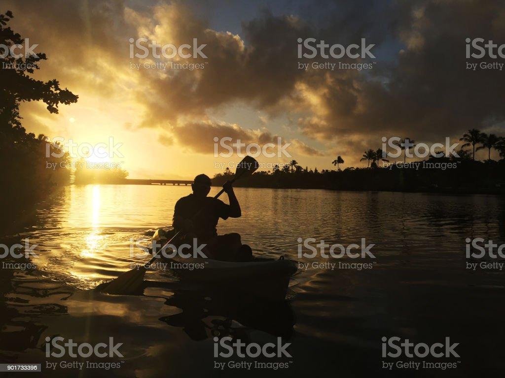 Man kayaks on Wailua River as early morning light baths the sky stock photo