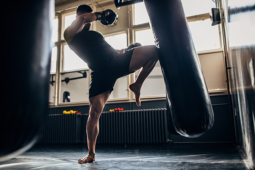 One man, kick boxer training alone in gym, kicking punching bag in gym.
