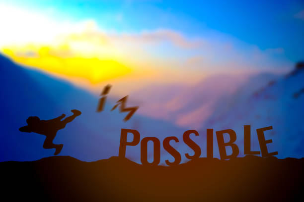man kicking impossible or possible over cliff on sunset background - possible stock photos and pictures