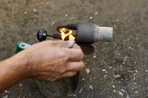 istock A man kindles a flame at the old rusty blowtorch. 1257550752