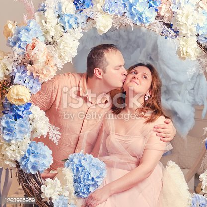 A man kisses a woman in a pink dress, studio portrait. Couple man and woman on a swing in flowers.