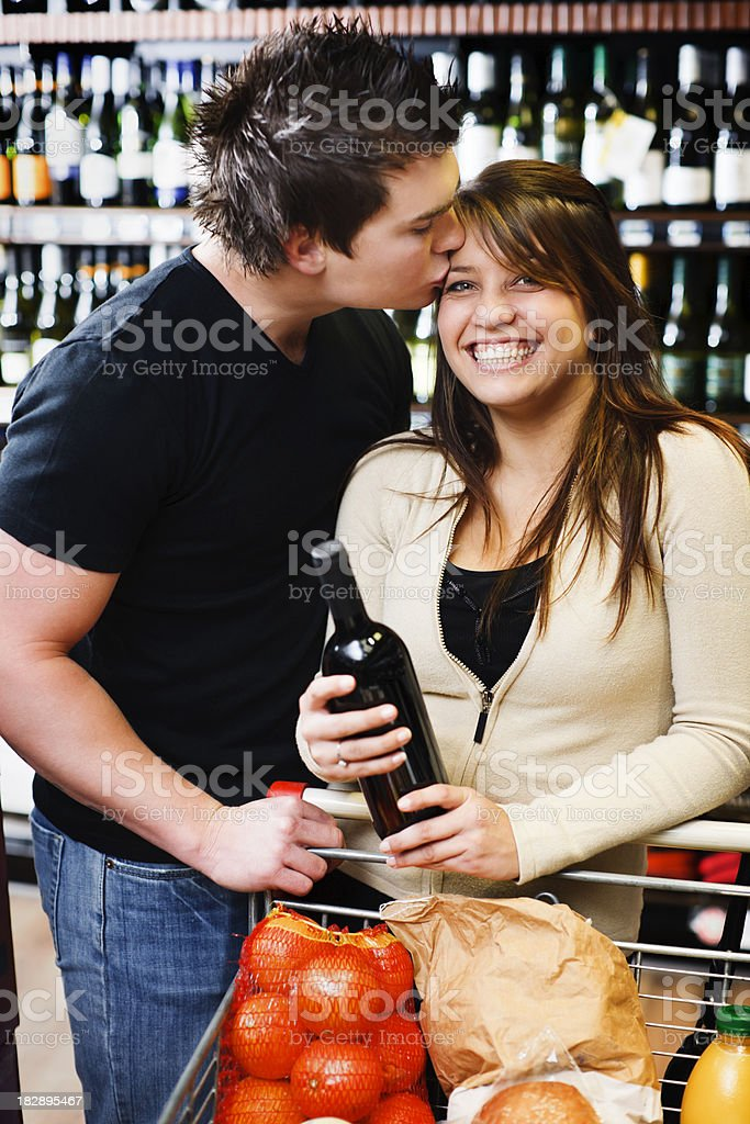 Man kisses his pretty partner in supermarket wine department royalty-free stock photo