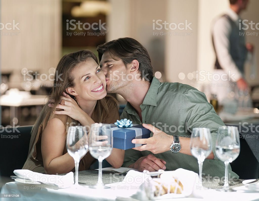 Man kissing and giving gift to woman in restaurant stock photo