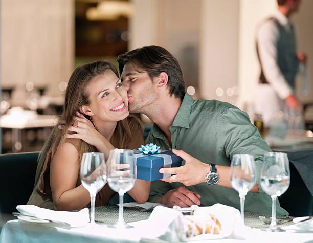hombre besando a la mujer dando regalos a y en el restaurante - cena romantica fotografías e imágenes de stock