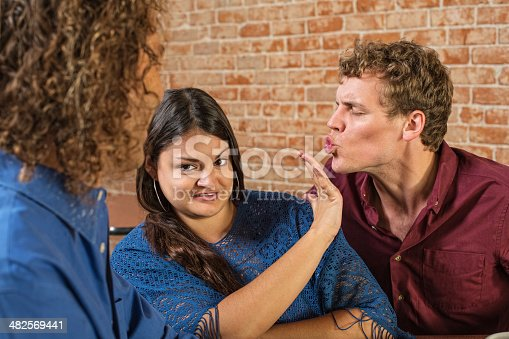 Annoyed woman being kissed by European male