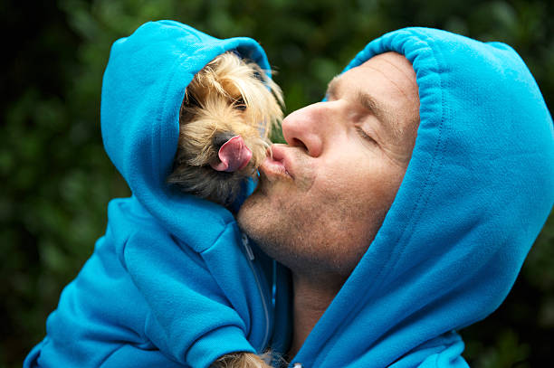 Man Kissing Best Friend Dog Matching Blue Hoodies at Park stock photo
