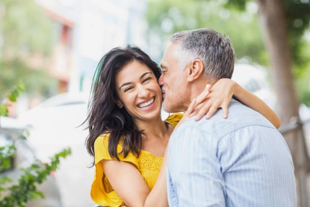 Man kissing cheerful woman stock photo
