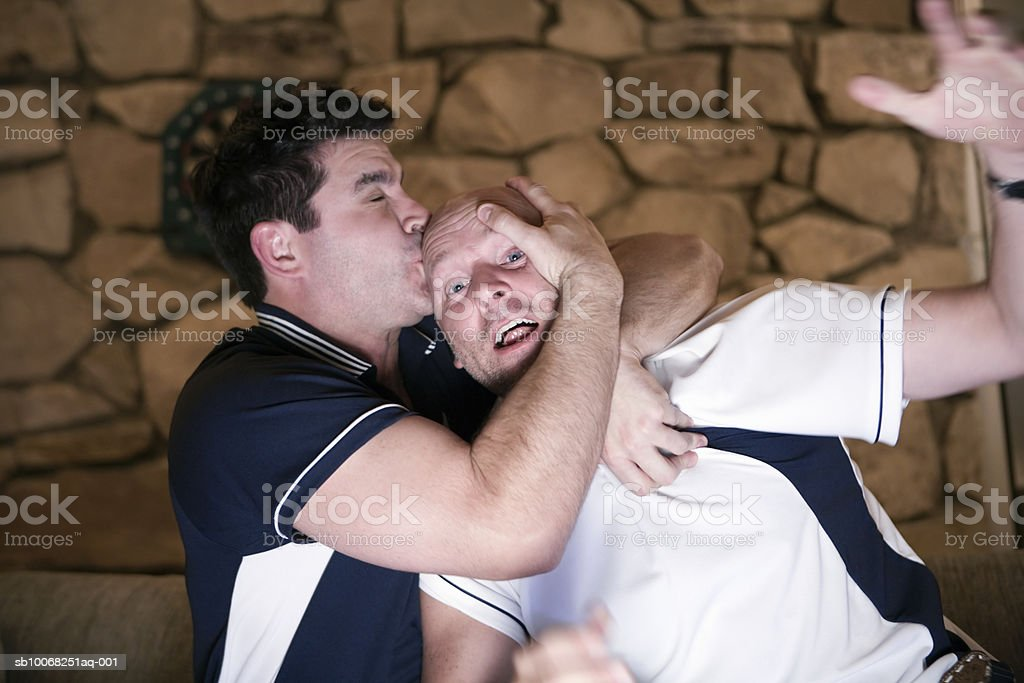 Man kissing friend on forehead at home royalty-free stock photo