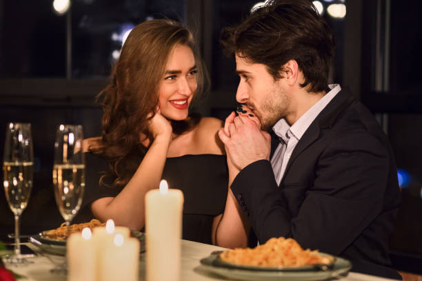 Man kissing hand of his girlfriend. Handsome man kissing hand of his girlfriend in restaurant during romantic dinner kissinghand stock pictures, royalty-free photos & images