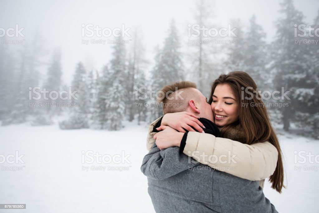 Man kissing his girlfriend and hugging her tightly stock photo