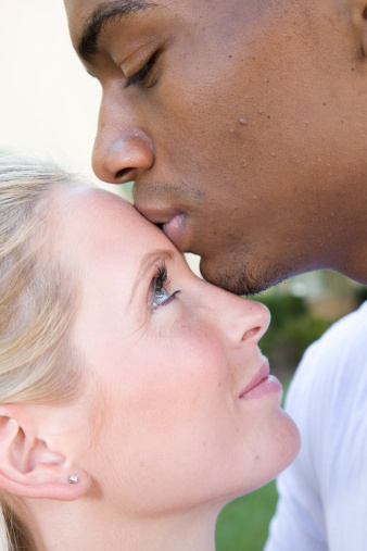 Man Kissing His Girlfriend On The Forehead Stock Photo