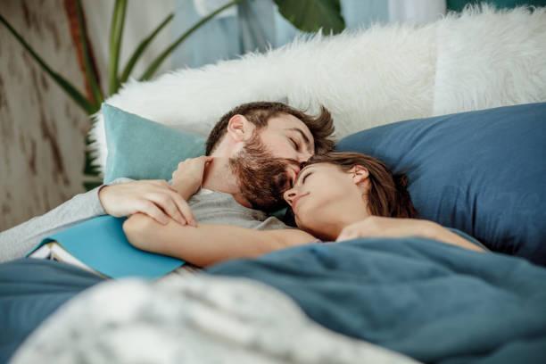 Mann küsst seine Freundin, während er im Bett liegt – Foto