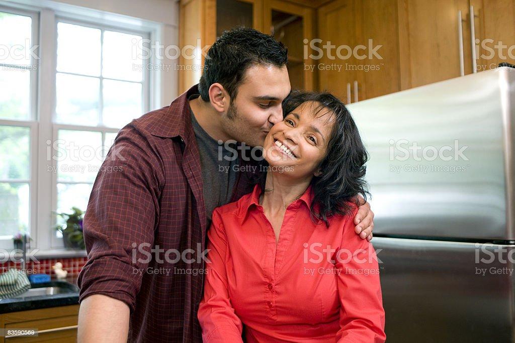 Man kissing his mother on cheek in kitchen royaltyfri bildbanksbilder