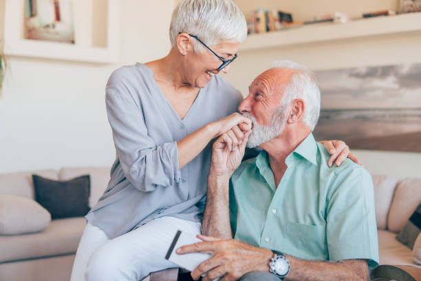 Man kissing his wife's hand Happy old woman having her hand kissed kissinghand stock pictures, royalty-free photos & images