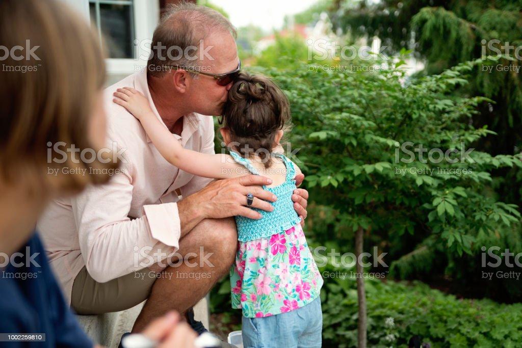 Man kissing little girl on family gathering. stock photo