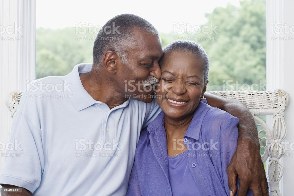 Man kissing wife stock photo