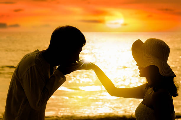 Man kissing woman hand with sea sunset background Man kissing woman hand with sea sunset background .Silhouette of happy couple at sunset  horizon over andaman sea sun shining through dresses stock pictures, royalty-free photos & images