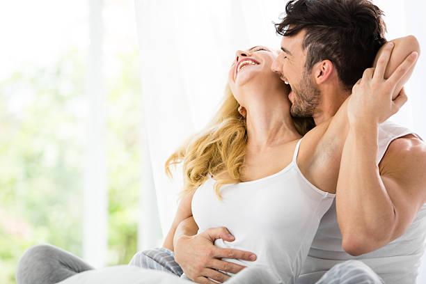 男にキスをする女性のベッド ストックフォト