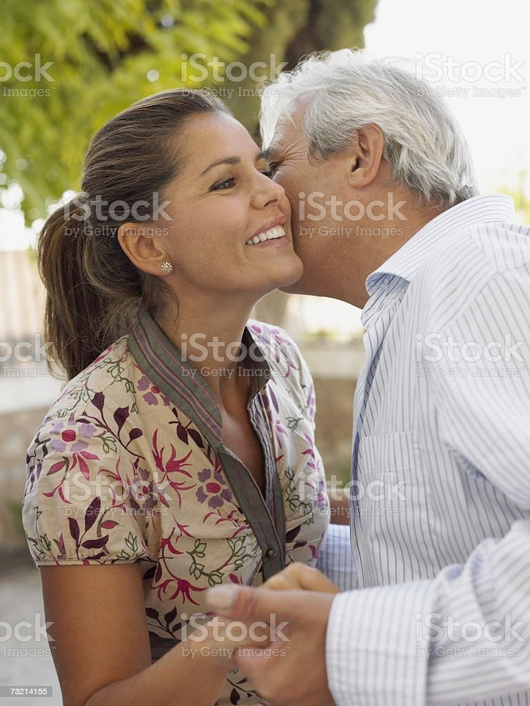 Man kissing woman on cheek stock photo