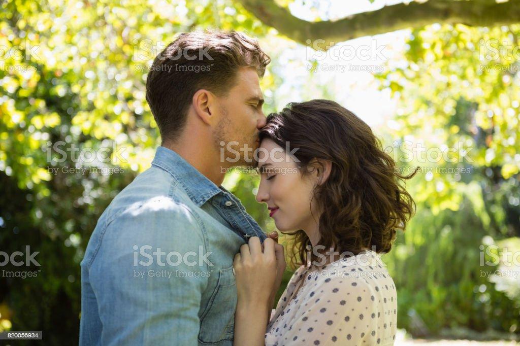 Hombre Besando a la mujer en la frente - foto de stock