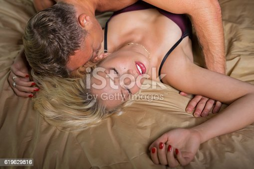 istock Man kissing woman on her neck during foreplay 619629816