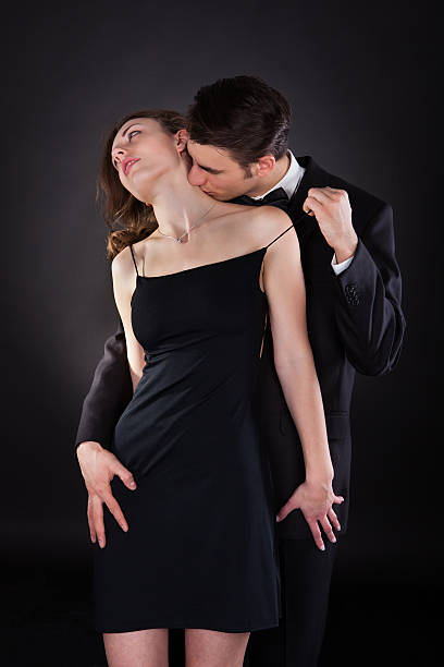 man kissing woman on neck while removing dress strap - kissing on neck stock photos and pictures