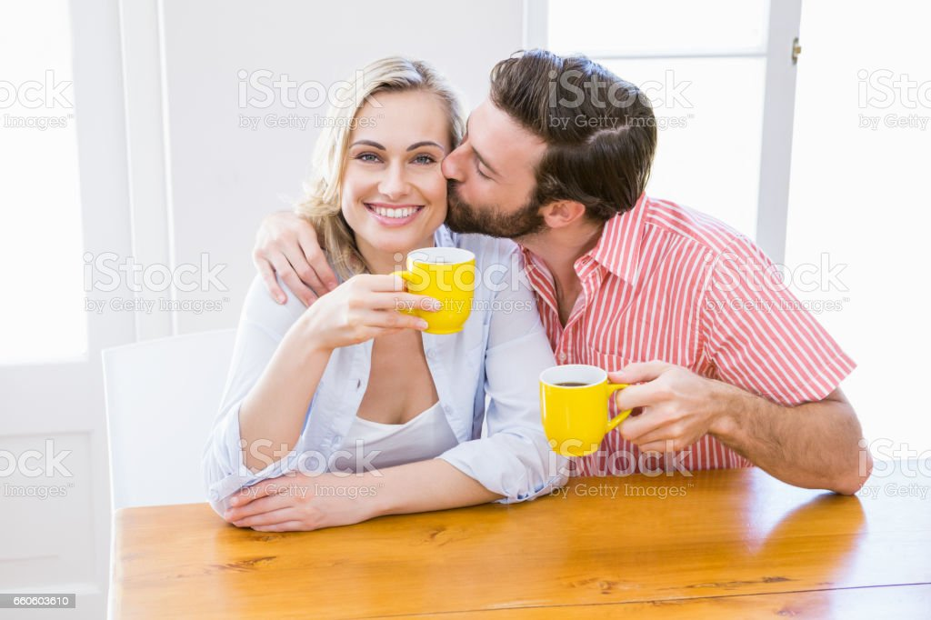 Man kissing woman while having coffee royalty-free stock photo