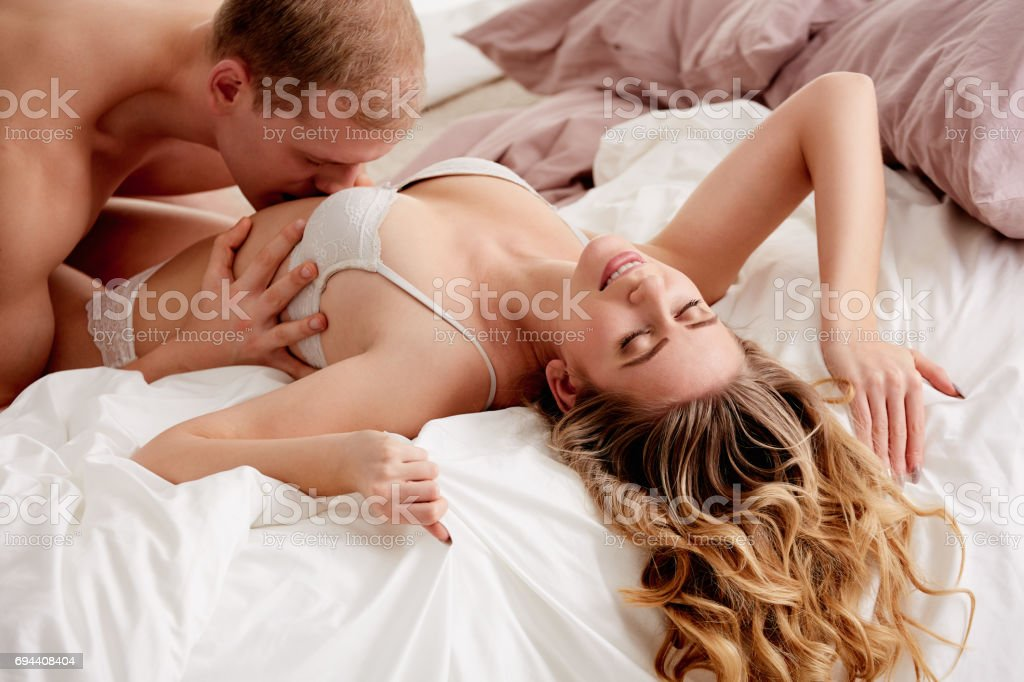 Man kissing woman's belly stock photo