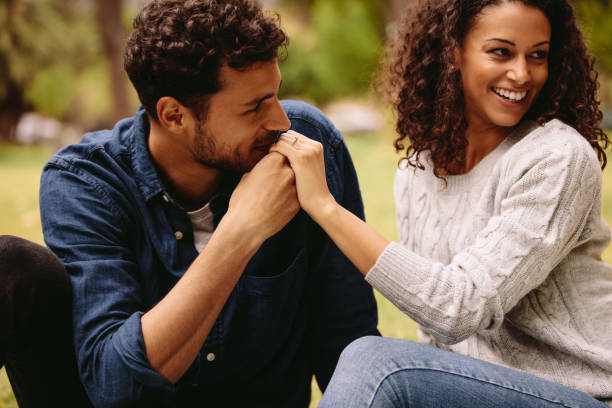 Man kissing woman's hand Young man kissing the hand of his girlfriend while sitting at the park. Man makes a marriage proposal and kisses the hand of a woman. kissinghand stock pictures, royalty-free photos & images