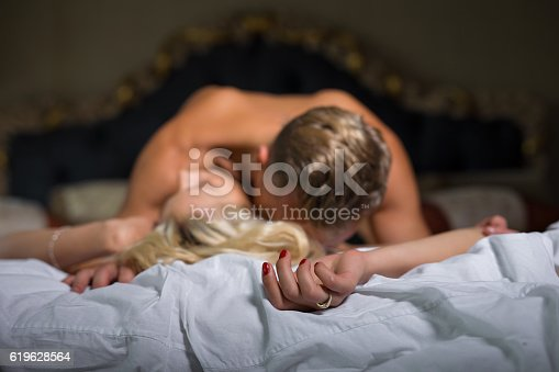 istock Man kissing womans neck while she is lying down 619628564