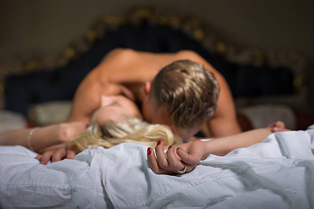 man kissing womans neck while she is lying down - platzierung der möbel stock-fotos und bilder