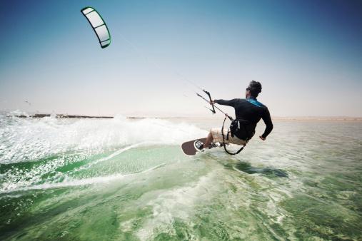 Man kiteboarding on choppy waves