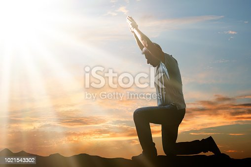 Side View Of A Man Kneeling And Praying Against Cloudy Sky At Sunset