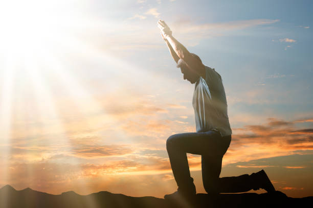 man kneeling and praying at sunset - praise and worship stock photos and pictures