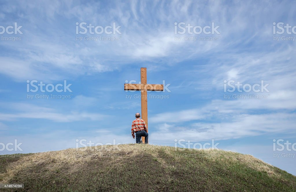 man kneeling by a wooden cross on a hill stock photo