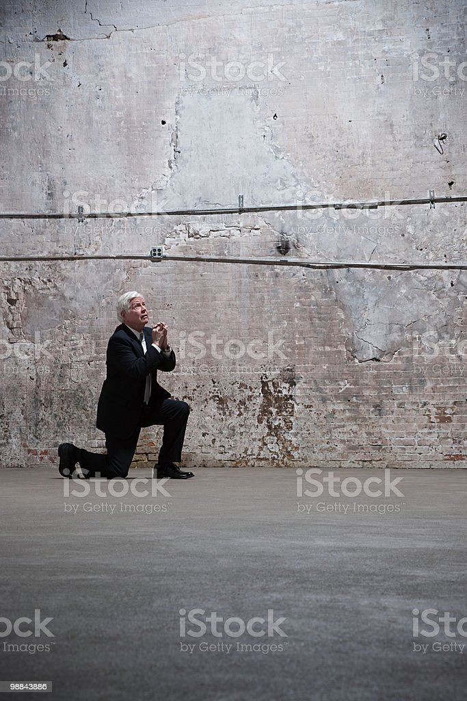 Man kneeling in warehouse royalty-free stock photo