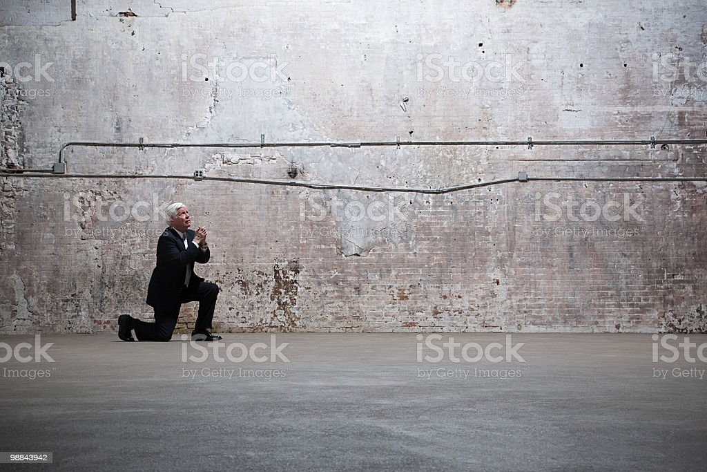 Man kneeling in warehouse royalty-free stock photo